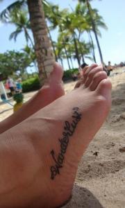 Красивая татуировка надпись на стопе у девушки.