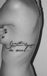 Симпатичная  татуировка надпись набитая на ребрах  молодой девушки.